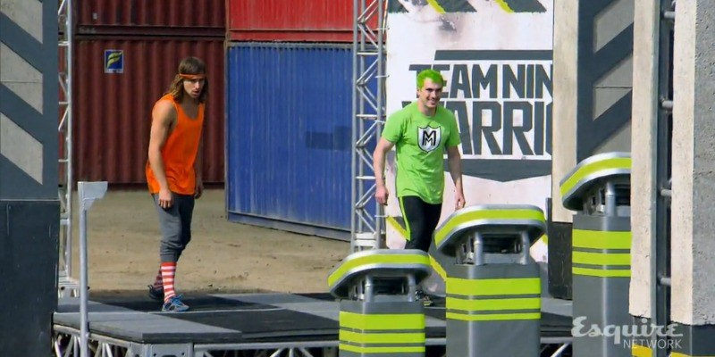 Jake Murray and Adam Grossman are in a runner's stance on the course of Team Ninja Warrior.