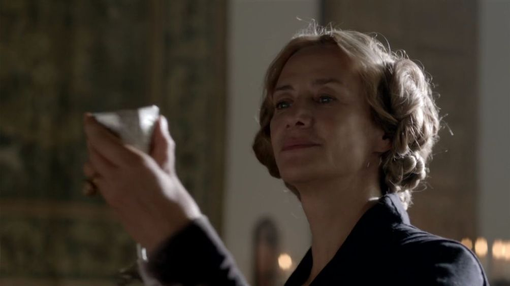 Janet McTeer holds up a chalice, while smiling