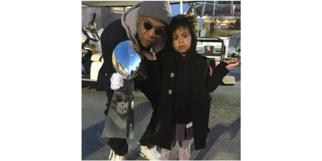 Jay Z holds up the Superbowl trophy while Blue Ivy shrugs with her hands out in a photo posted to Beyonce's Instagram account.
