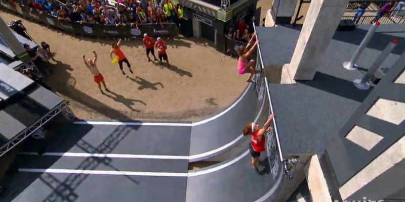 Jennifer Tavernier and Jeri D'Aurelio are climbing up the Warped Wall as everyone watches.