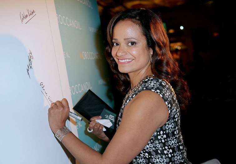 Judy Reyes smiling and signing a white board