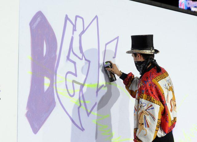 Justin Bieber spray paints the word 'Believe' onto a white wall.