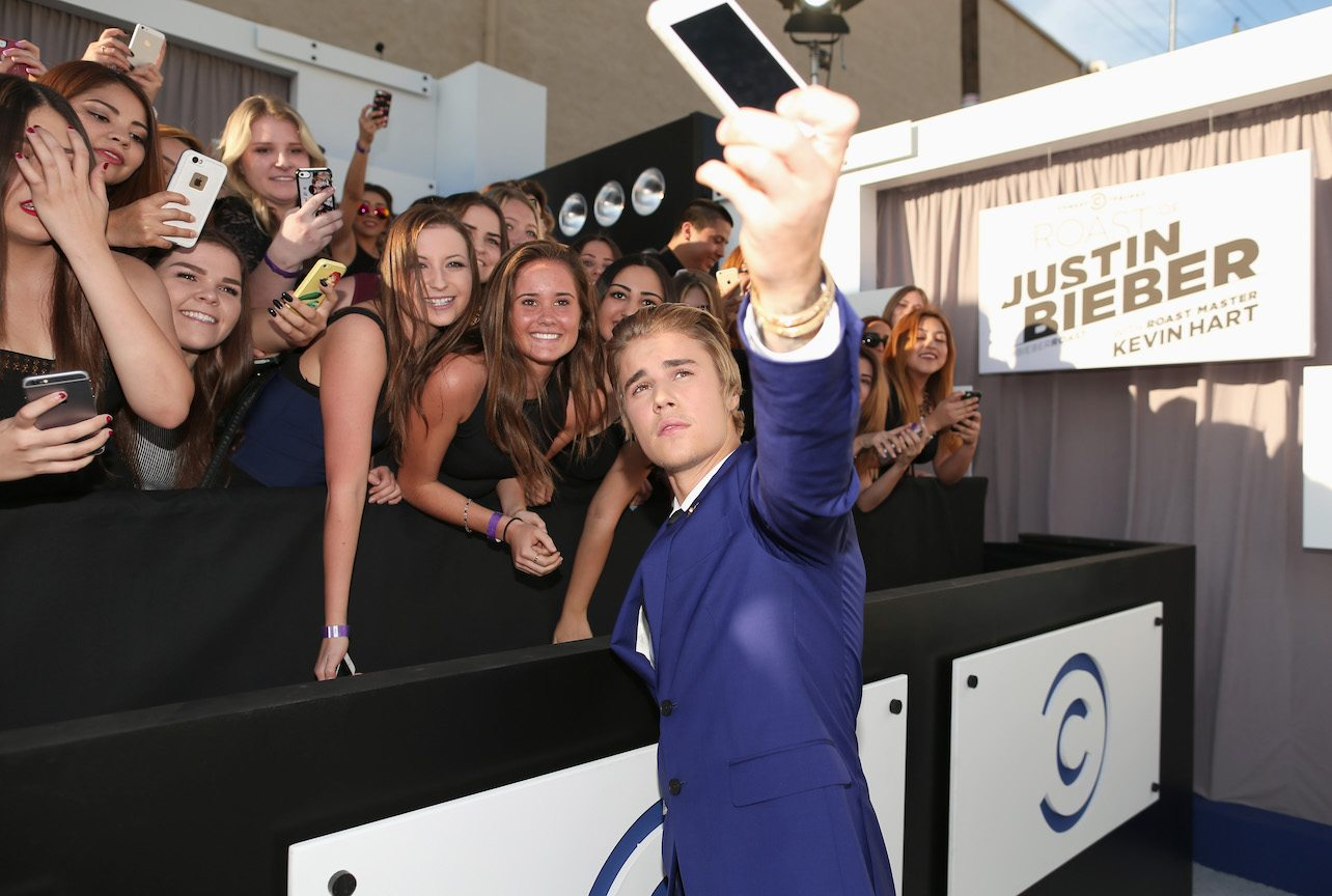 Justin Bieber takes a selfie with a group of fans while he stands on the red carpet before the Comedy Central Roast of Justin Bieber.