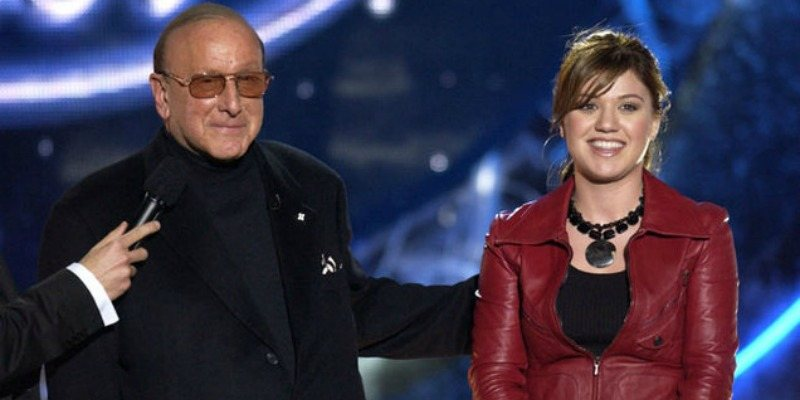 Clive Davis and Kelly Clarkson are standing next to each other on stage of American Idol.