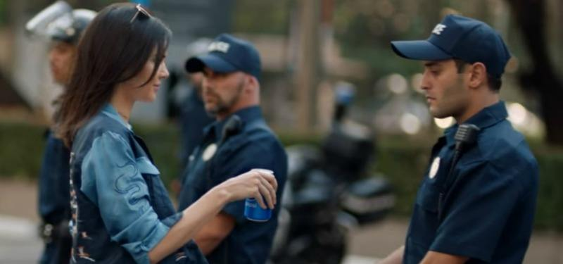 Kendall Jenner is handing a police man a Pepsi.