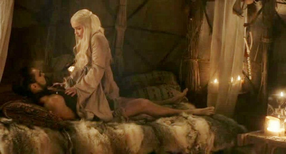 Daenerys mounted on top of Khal Drogo, who lays prone in bed with her naked.