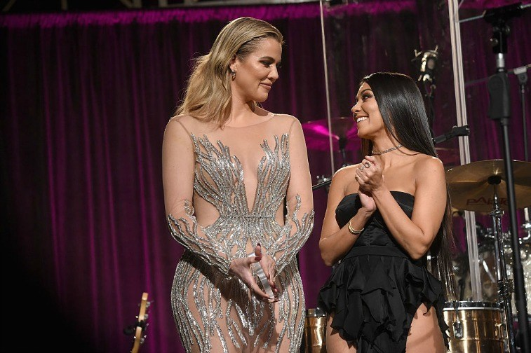 Khloe and Kourtney Kardashian onstage in fancy attire in front of musical instruments and a fuchsia curtain