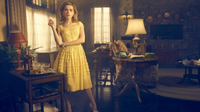 B.D. Hyman stands in an front of a minibar in an old-fashioned living room, wearing a yellow dress, in a promotional image from the FX series 'Feud.'