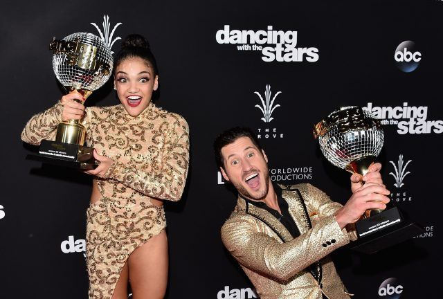 Laurie Hernandez and Val Chmerkovskiy stand on the red carpet and hold their mirror ball trophies after winning 'Dancing With the Stars.'