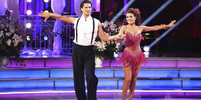 Lisa Vanderpump and Gleb Savchenko are holding hands while dancing on the show.