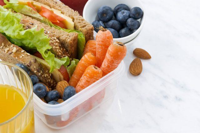 Sandwiches, carrots and veggies in a Tupperware container.