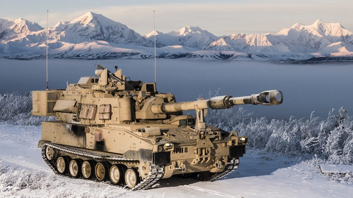 A M109A7 tank drive along a snow covered road.