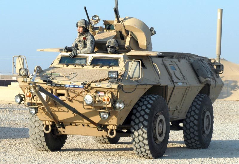 Soldiers look out of the top of an M117 Guardian.
