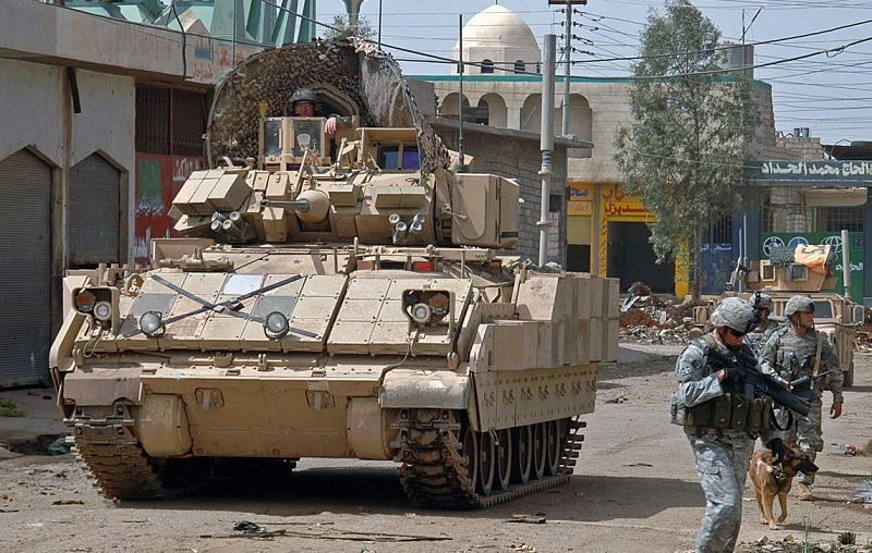 An M2 Bradley Fighting Vehicle rolls down a street while soldiers walk nearby.