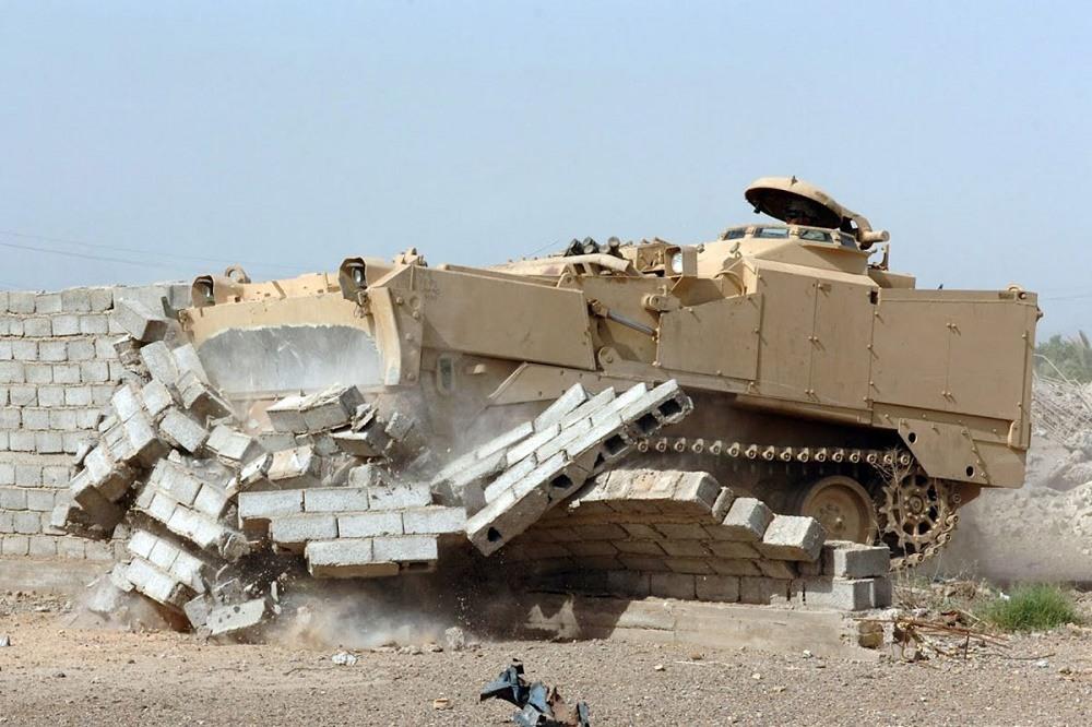 An M9 Armored Combat Earthmover plows through a wall.