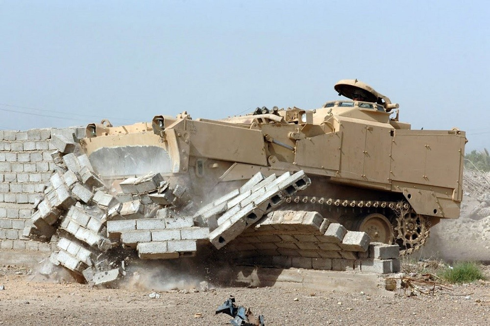 An M9 Armored Combat Earthmover plows through a wall.