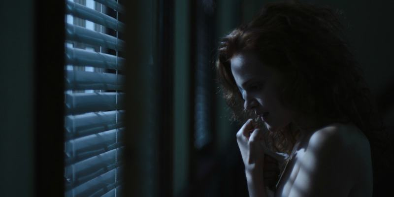 Janine has a bandage over her eye and is standing in front of a window at night.