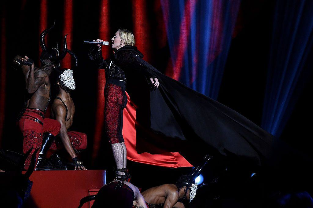 Singer Madonna onstage wearing a matador costume singing into a microphone with dancers dressed as bulls around her