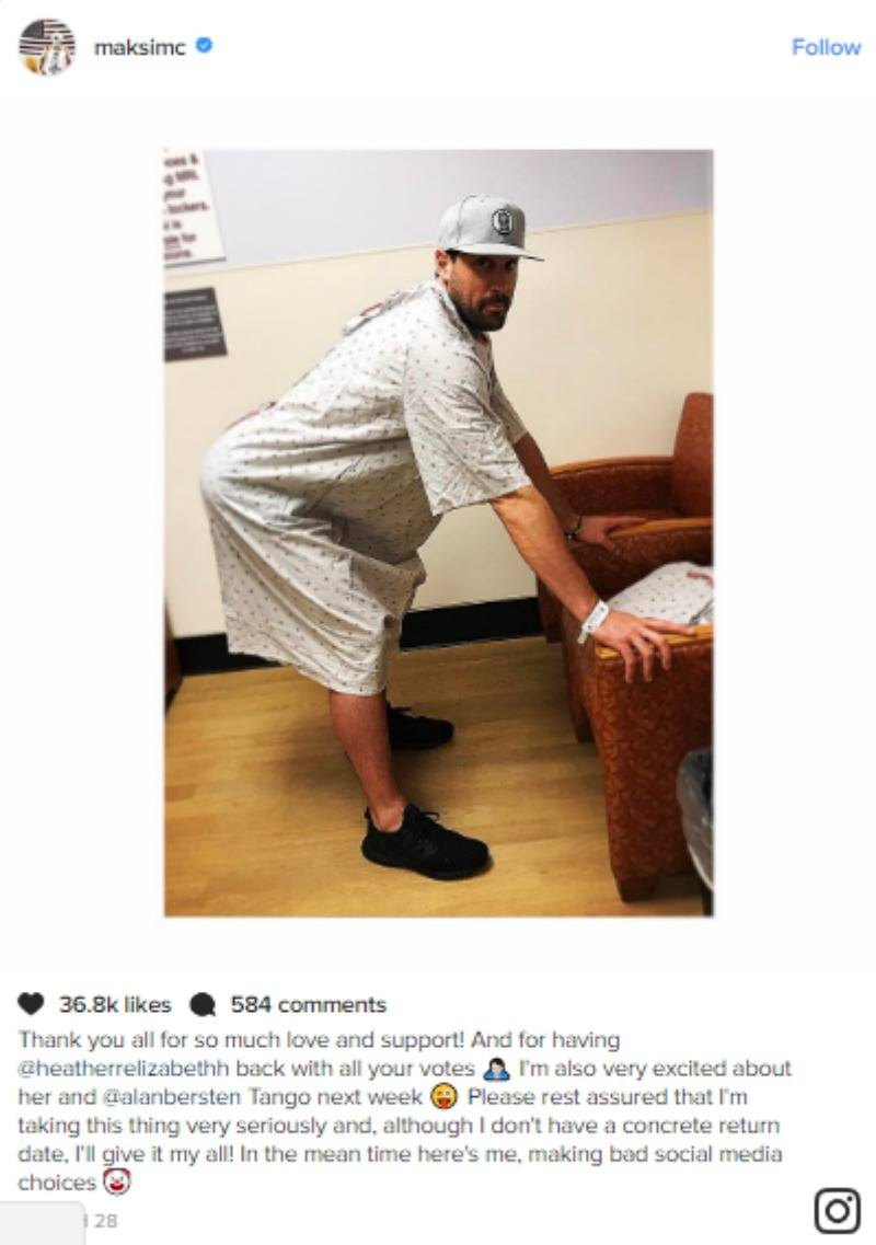 Maksim Chmerkovskiy is in a hosptal gown and is leaning against a chair.