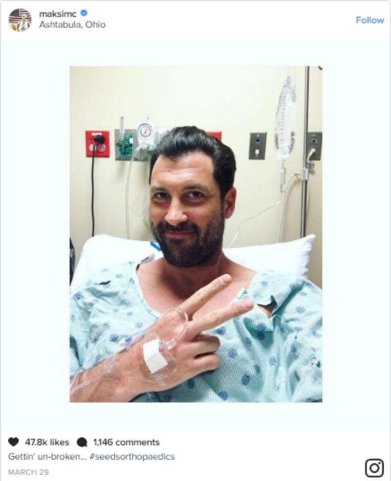 Maksim Chmerkovskiy is making a peace sign from a hospital bed and smiling.