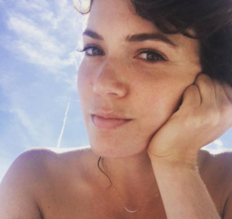 Mandy Moore is leaning her head on one hand in a makeup-free selfie.