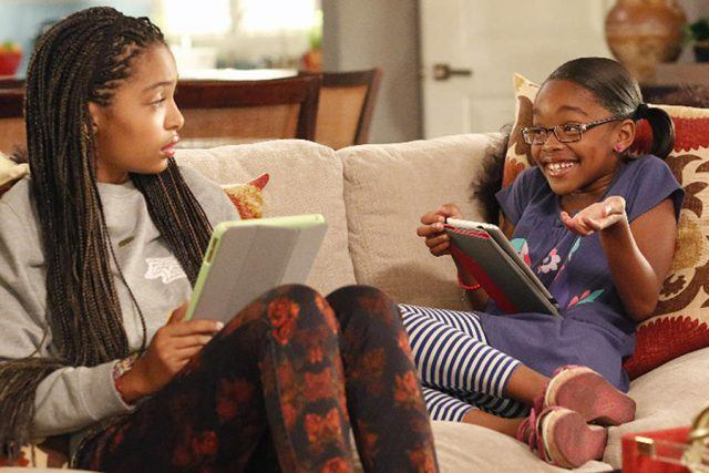 Zoey looks at Diane, who shrugs while smiling, as they both hold tablets and sit on a couch in a scene from the ABC comedy 'Black-ish.'