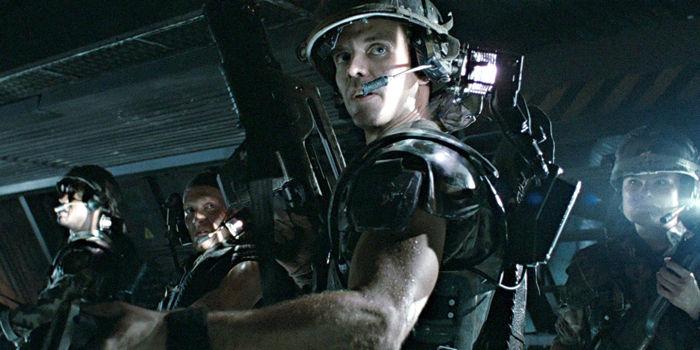 Michael Biehn dressed as a soldier, looking behind his left shoulder in a dark corridor