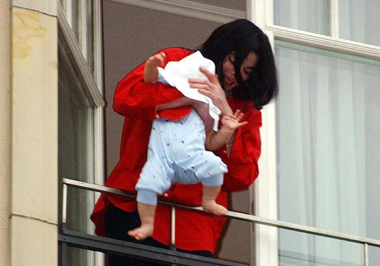 Michael Jackson holding his baby over a balcony