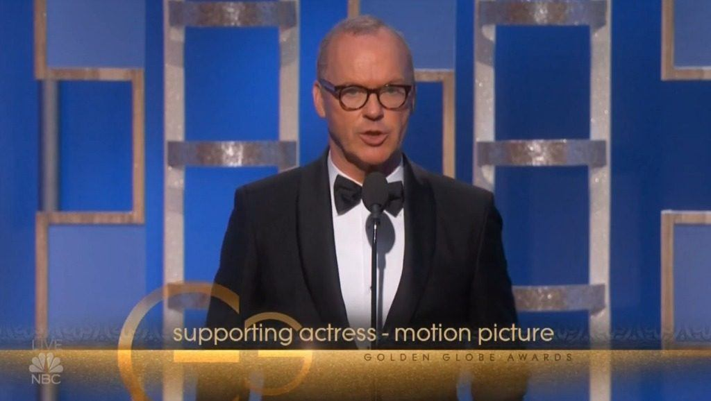 Actor Michael Keaton on stage wearing a tux and glasses presenting an award at The 74th Golden Globe Awards