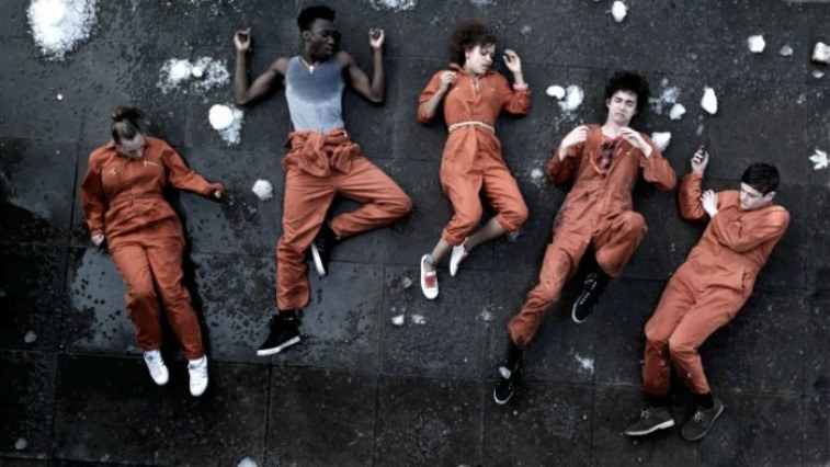 Lauren Socha as Kelly Bailey, Nathan Stewart-Jarrett as Curtis Donovan, Antonia Thomas as Alisha Daniels, Robert Sheehan as Nathan Young, and Iwan Rheon as Simon Bellamy lying on the ground in orange jumpsuits with snow around them in Misfits
