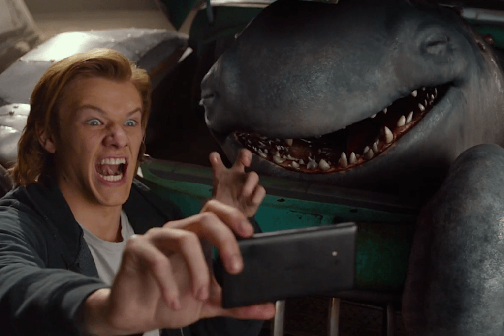 Lucas Till with his mouth open, taking a selfie with a shark-like monster