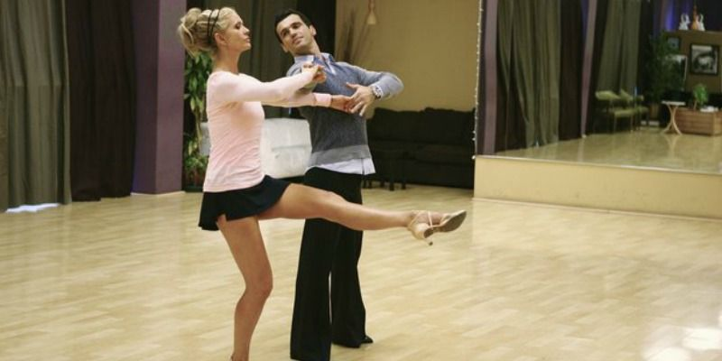 Nancy O'Dell is practicing a move with one leg in the air with Tony Dovolani.