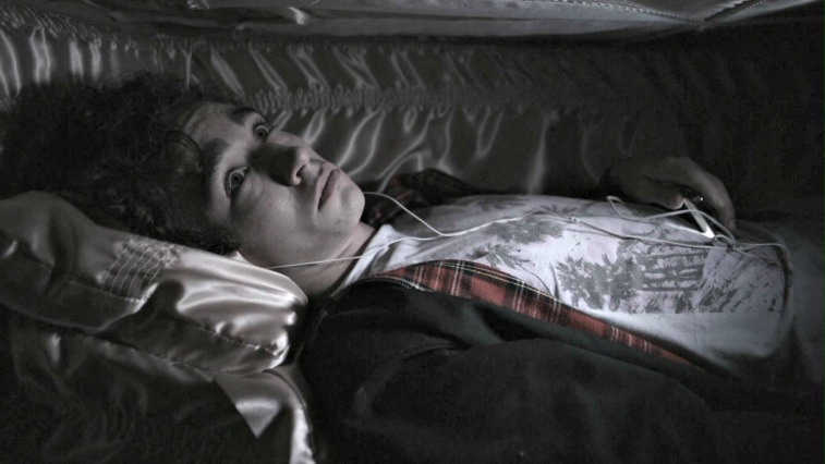 Robert Sheehan as Nathan Young with headphones in listening to an MP3 player in a coffin on Misfits