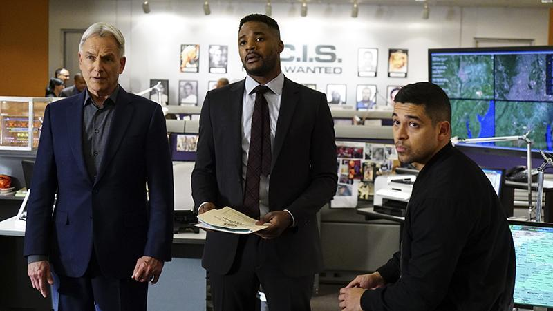 Mark Harmon, Henry Duane and Wilmer Valderrama stand next to each other in an office