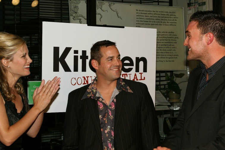 Two men and a woman speaking to one another in front of a sign for 'Kitchen Confidential'
