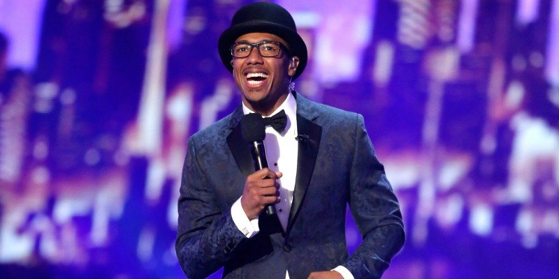 Nick Cannon is holding a microphone on stage of America's Got Talent.