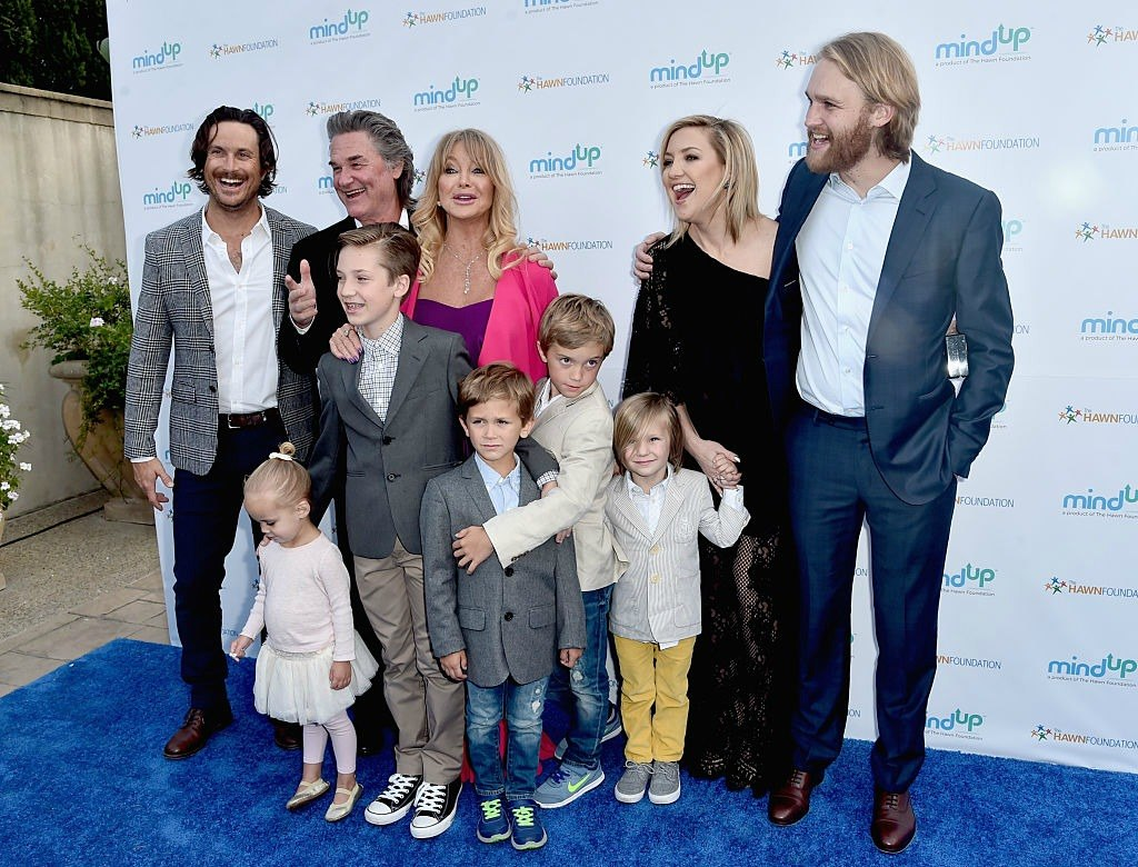 Actors Oliver Hudson, Kurt Russell, Goldie Hawn, Kate Hudson, Wyatt Russell, and five small children on a blue carpet laughing and posing