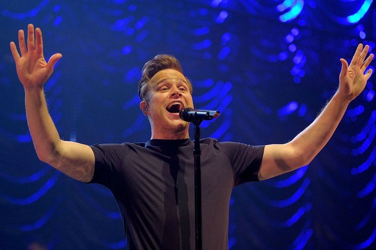 Man on stage singing into a microphone with his arms in the air