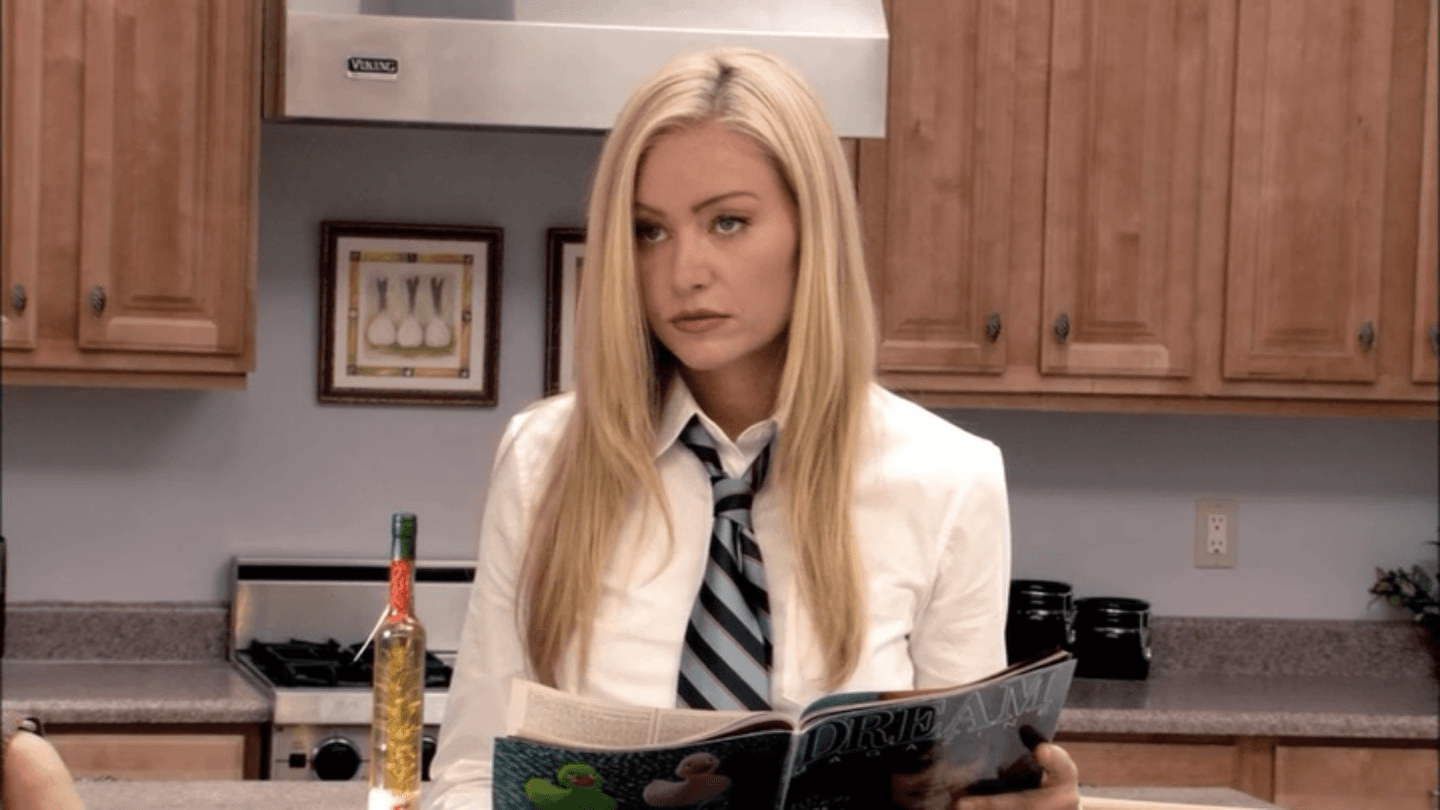 Portia de Rossi as Lindsay Bluth wearing a collared shirt and tie in a kitchen reading a magazine and staring ahead on Arrested Development