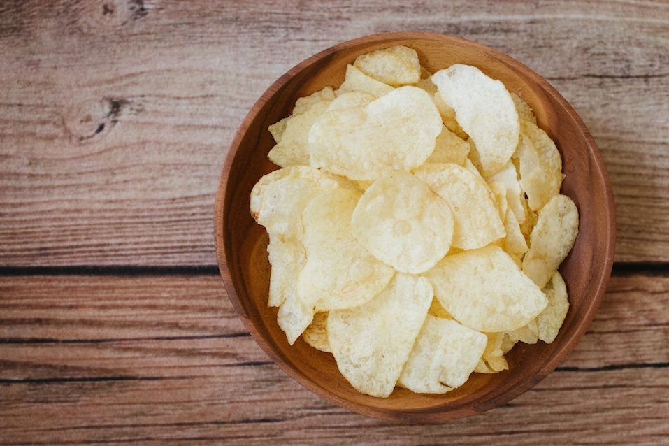 potato chips on light wooden background