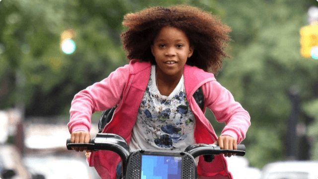 Annie, wearing a floral shirt and pink sweatshirt, looks happy as she rides a bike in a scene from the 2014 'Annie' remake.