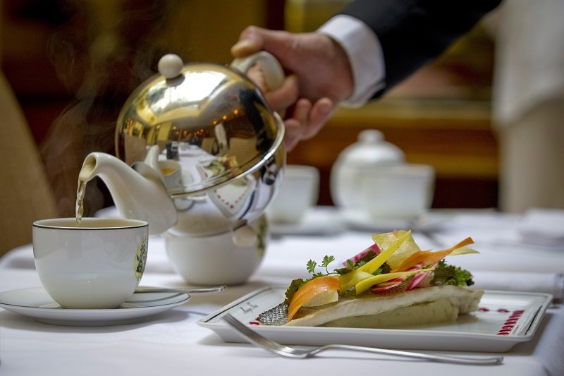pouring tea at a fancy restaurant table
