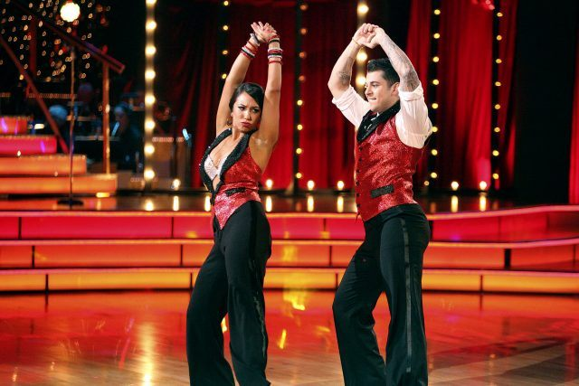 Cheryl Burke and Rob Kardashian dancing together on the dance floor with their hands up above their heads.