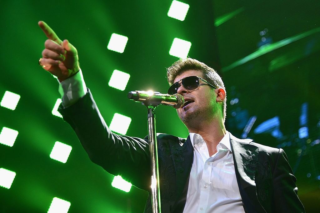 Singer Robin Thicke on stage wearing sunglasses and singing into a microphone while pointing