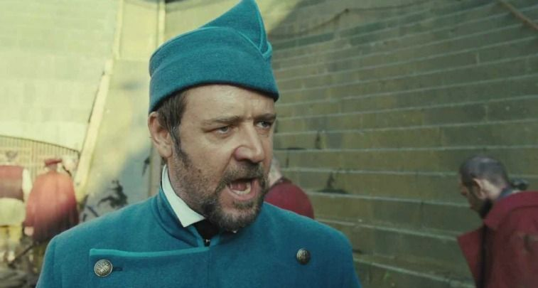 Russell Crowe as Inspector Javert in a blue jacket and cap yelling in Les Misérables
