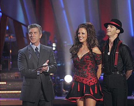 Tom Bergeron, Sara Evans, and Tony Dovolani stand on stage smiling on 'Dancing With the Stars.'
