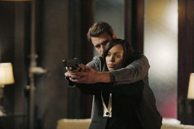 Jake teaches a weary-looking Olivia how to hold a gun in a scene from 'Scandal.'