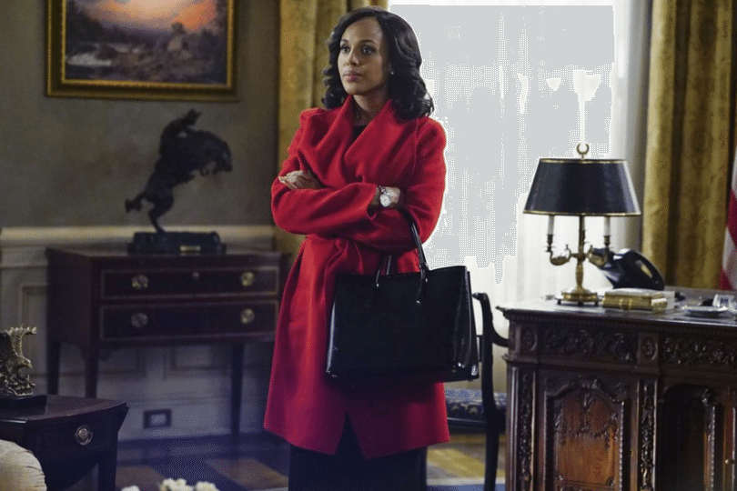 Kerry Washington's Olivia Pope stands next to a desk in a red coat in a scene from Scandal