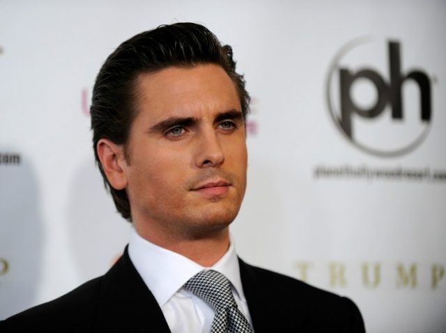 Scott Disick poses in a black suit and patterned tie.