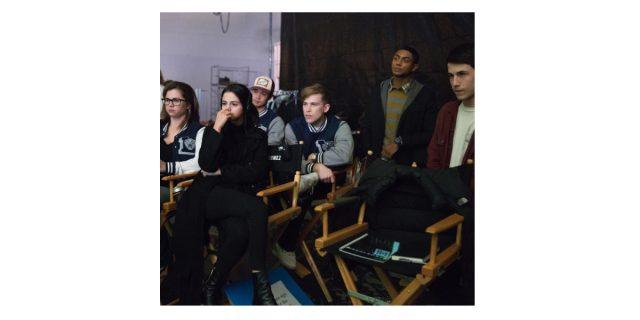 Selena Gomez sits in a director's chair as '13 Reasons Why' cast members stand around her on the set of the series.
